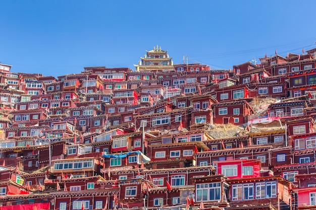 日の出日と背景のlarung gar(仏教学院)でトップビュー修道院は青い空、四川省、中国です。