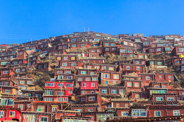 日の出日と背景のlarung gar(仏教学院)で赤い修道院は青い空、中国四川省です。