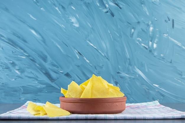 Fogli di lasagna in una ciotola su un asciugamano, sullo sfondo di marmo.