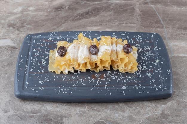 Fogli di lasagne con pomodoro al forno sul vassoio di legno, sul piano di marmo.