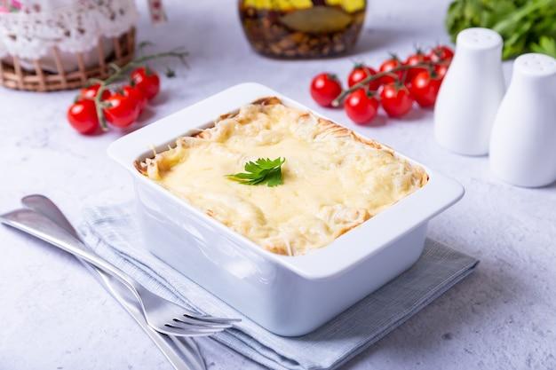 Лазанья с болоньезе и соусом бешамель в белой порционной форме. традиционное итальянское блюдо, домашнее. крупный план.