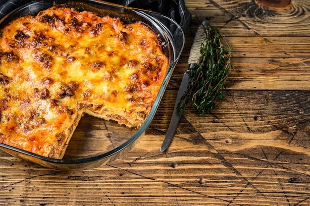 베이킹 접시에 볼로네제 소스와 다진 쇠고기를 곁들인 라자냐. 나무 배경입니다. 평면도. 공간을 복사합니다.