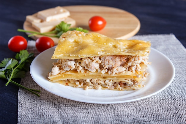 Lasagna with minced meat and cheese on black wooden background.