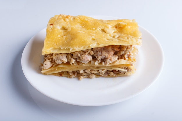 Lasagna with minced meat and cheese isolated on white background.