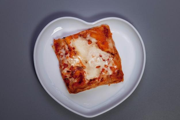 어두운 회색 배경에 야채와 함께 라자냐입니다. 야채와 함께 라자 냐와 양식 마음에 하얀 접시에 전통 음식 건강. 맛있는 건강식 다이어트. 복사 공간
