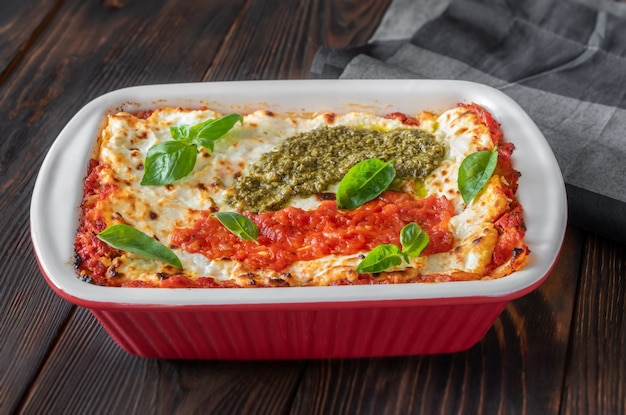 Lasagne topped with tomato sauce and pesto in baking pan