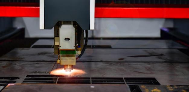 공장에서 불꽃으로 판금을 절단하면서 레이저 절단 헤드 기계