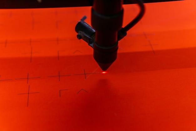Лазерная режущая головка промышленного станка прорезает оранжевый лист фанеры, крупный план