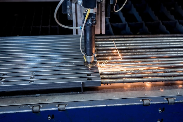 The laser cutting machine cutting the holes on pipes.