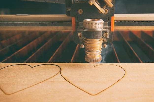 Laser cutting machine is cutting hearts in the wooden plank