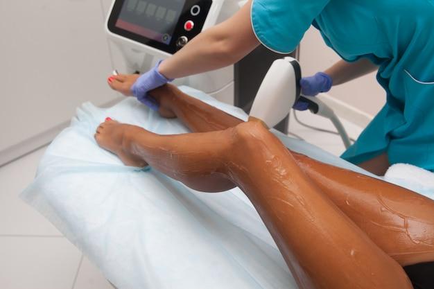 Лазерная эпиляция и косметология в салоне красоты. процедура удаления волос. лазерная эпиляция, косметология, спа и эпиляция. красивая женщина получает удаление волос на ногах