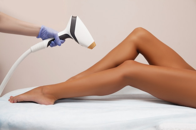 Laser epilation and cosmetology in beauty salon. hair removal procedure. laser epilation, cosmetology, spa, and hair removal concept. beautiful woman getting hair removing on legs