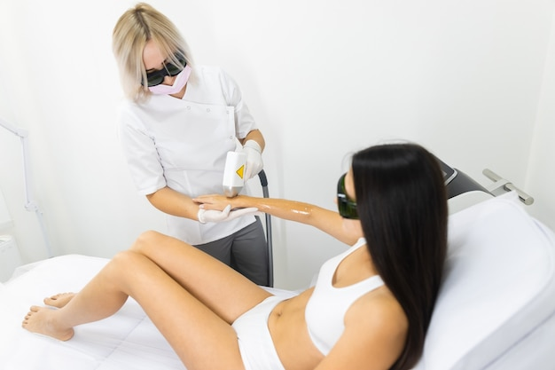 Laser epilationl salon worker removes hair from female patient's hands