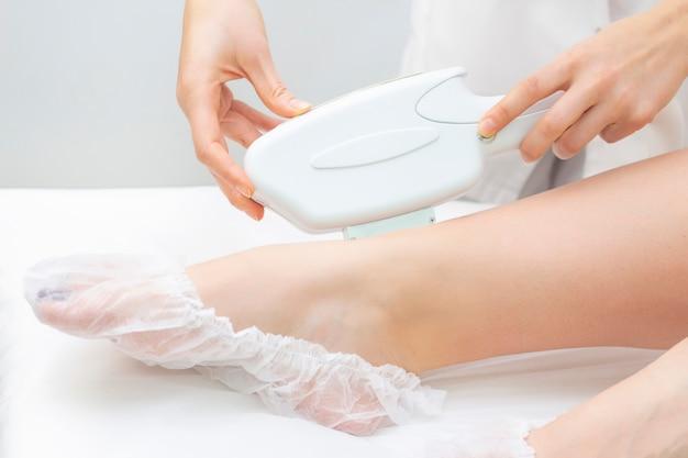 Лазерное удаление волос. девушка снимает волосы с лазера на ногах в спа салоне. мастер держит лазер и удаляет волосы.