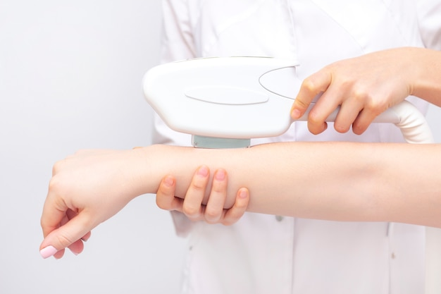 Laser hair removal. the girl removes hair with a laser on her arm in a spa salon.