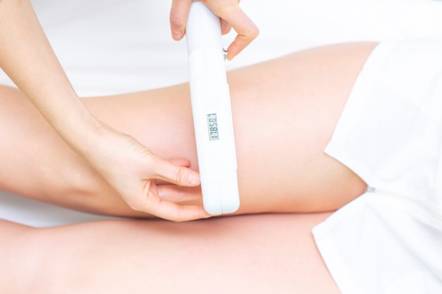 Laser hair removal. the girl removes hair with a laser on her legs in a spa salon. the master holds a laser and removes hair.