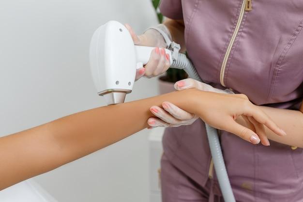 Лазерная эпиляция в действии косметолог делает лазерную эпиляцию на руке женщины