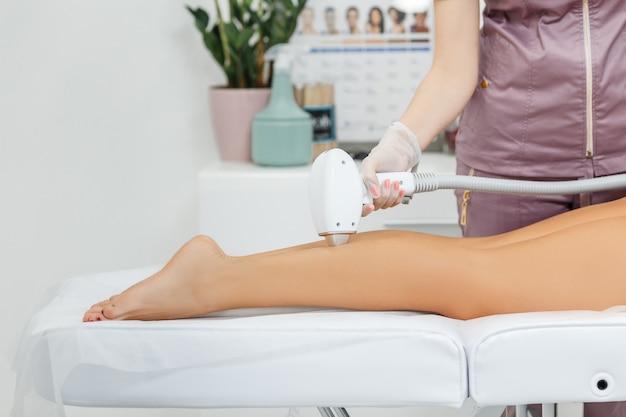 Лазерная эпиляция в действии косметолог делает лазерную эпиляцию женских ног с обезболивающим гелем