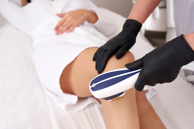 Laser hair removal on ladies legs in beauty salon