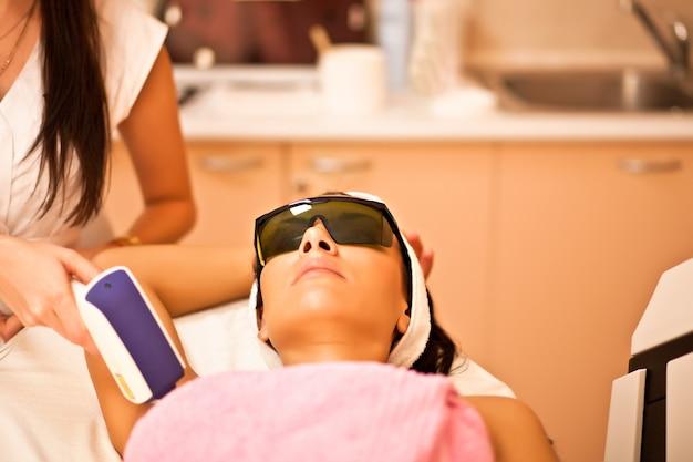 Лазерная эпиляция подмышек женщины. женщина, имеющая лечение лазерной эпиляции в салоне.
