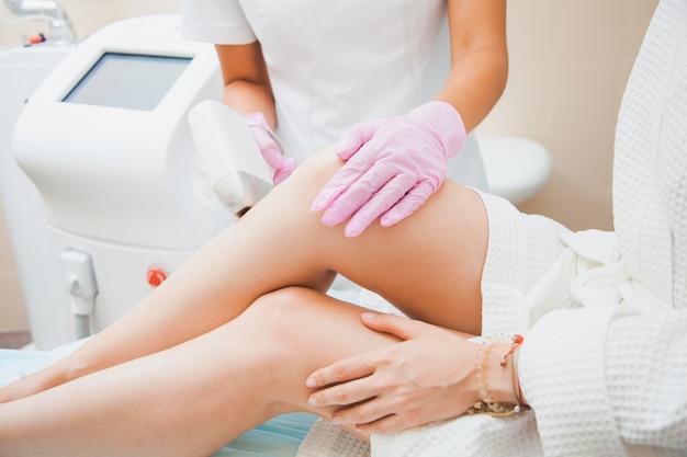 Лазерная эпиляция, фотоэпиляция, концепция ухода за телом и кожей. молодая женщина удаляет волосы на ногах в косметологической клинике. снимок крупным планом, до неузнаваемости женщина