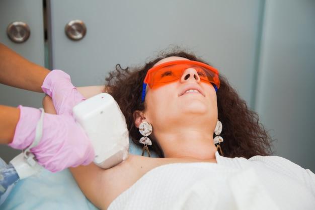 Лазерная эпиляция, фотоэпиляция, концепция ухода за телом и кожей. молодая женщина удаляет волосы на ногах в косметологической клинике.