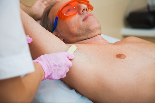 Laser hair removal procedure for man. male person at cosmetologist office on total body depilation. smooth and healthy skin concept.