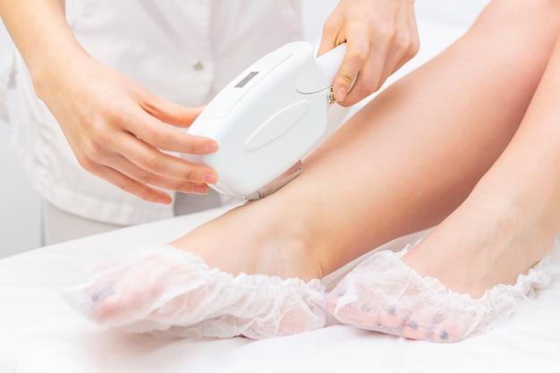 Лазерное удаление волос. девушка убирает волосы лазером на ногах в спа салоне. мастер держит лазер и удаляет волосы.