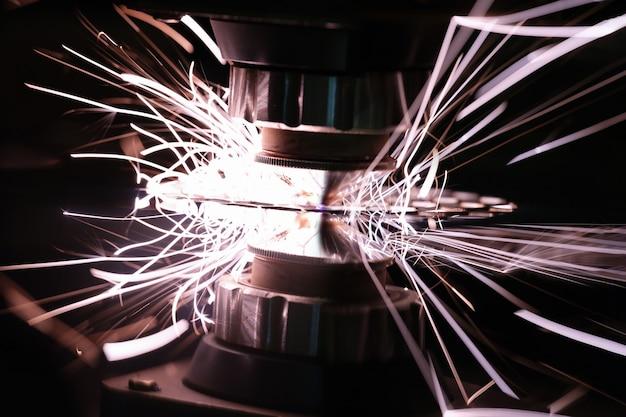 明るい火花のクローズアップで金属を切断するレーザーマシン