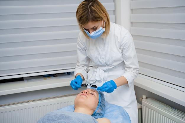 女性のためのレーザー光若返りと顔のカーボンピーリング。黒のフェイスマスク。皮膚科および美容学。外科用レーザーを使用します。
