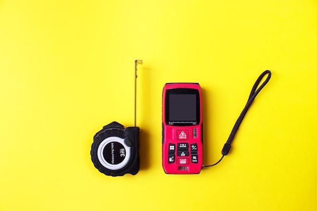 黄色の背景にレーザー距離計と巻尺。測定装置の概念。