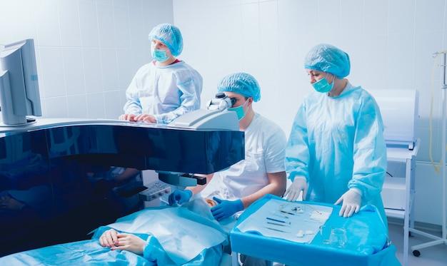 Лазерная коррекция зрения. пациент и команда хирургов в операционной во время офтальмологической операции. зеркало век. лазик лечение.