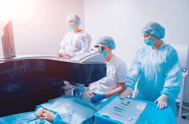 Laser vision correction. a patient and team of surgeons in the operating room during ophthalmic surgery. eyelid speculum. lasik treatment.