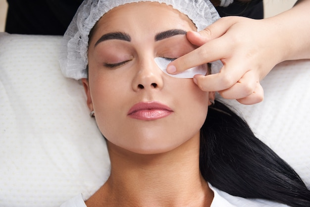 Lash laminating and painting closeup face beauty procedures in cosmetology clinic