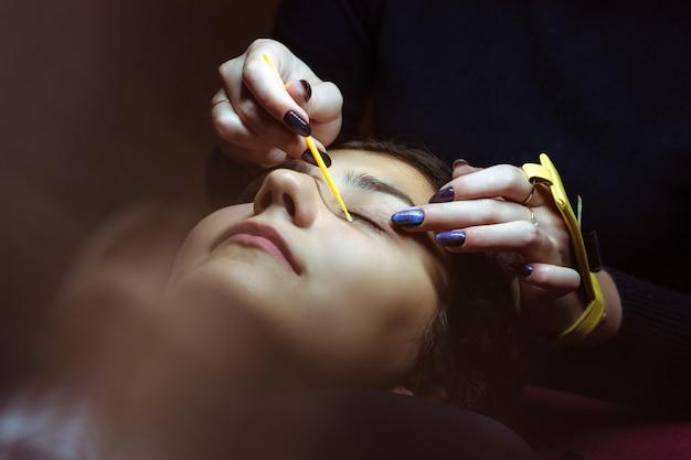 ラッシュ作りのプロセス、極端に長いまつ毛とピンセット、女性のまつげエクステ。