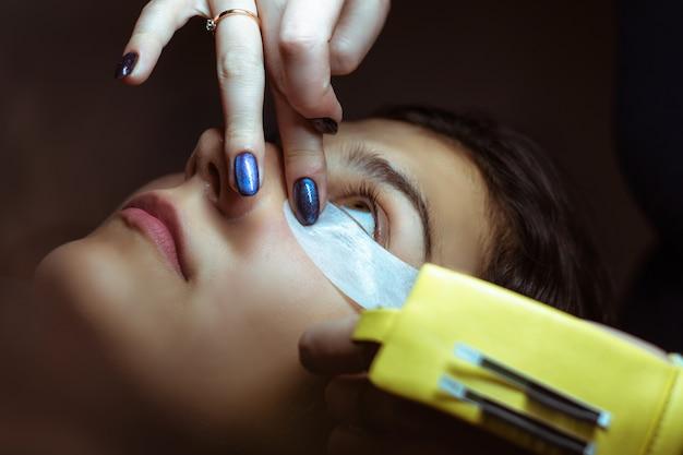 Lash making process, extreme long lashes and tweezers, woman eyelash extension. Premium Photo