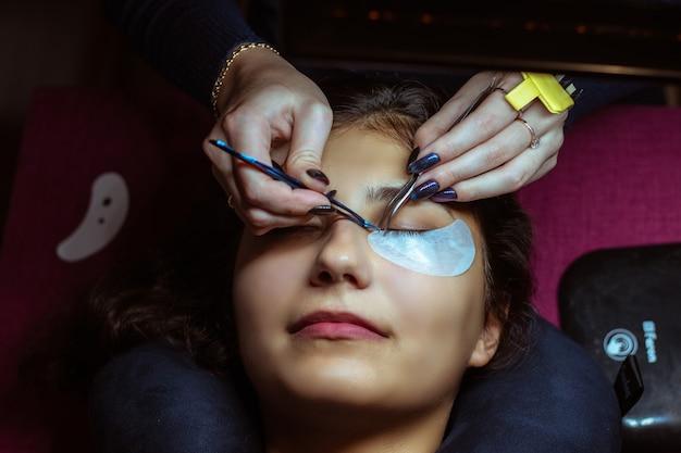 Lash making process, extreme long lashes and tweezers, woman eyelash extension.