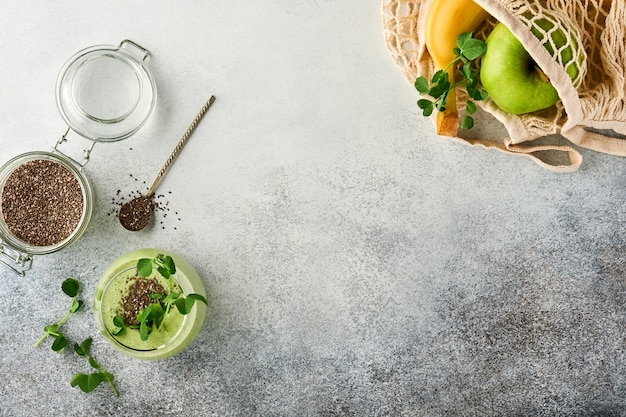 Маленькая здоровая зеленая смузи и ингредиенты для смузи, свежий шпинат, семена чиа, микрозелень гороха, банан, киви и яблоко в многоразовых сумках для покупок на светло-сером бетонном фоне. вид сверху.