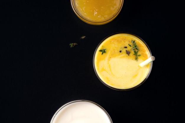 Lassi mango drink next to jam and yogurt on black