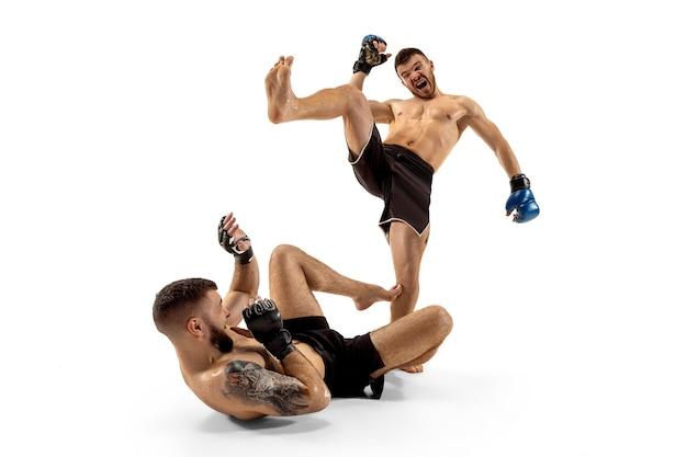 勝つ最後のチャンス。白いスタジオの背景に孤立してポーズをとる2人のプロの戦闘機。健康な筋肉質の白人アスリートまたはボクサーのカップルが戦っています。スポーツ、競争、人間の感情の概念。