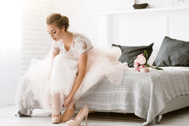 The last minutes. charming delighted young bride sitting on the bed in white colored room while wearing her shoes and expressing tenderness