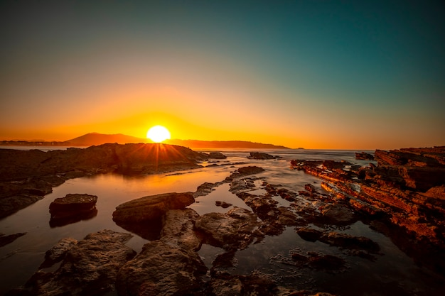 太陽を背景にしたアンダイエの干潮時の秋の夕日の最後の瞬間