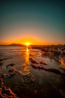 주황색 일몰에 hendaye 바위에서 태양의 마지막 순간. 프랑스