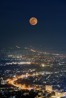 The last penumbral lunar eclipse in 2020 over chiang mai city at night , aerial view city night from the view point on top of mountain