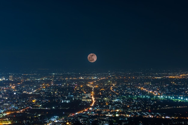 The last penumbral lunar eclipse in 2020 over chiang mai city at night , multiple exposure