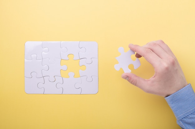 Last piece jigsaw in hand white puzzle