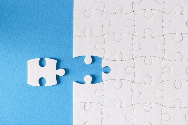 青い背景の上に別々に横たわっているパズルの最後のピース