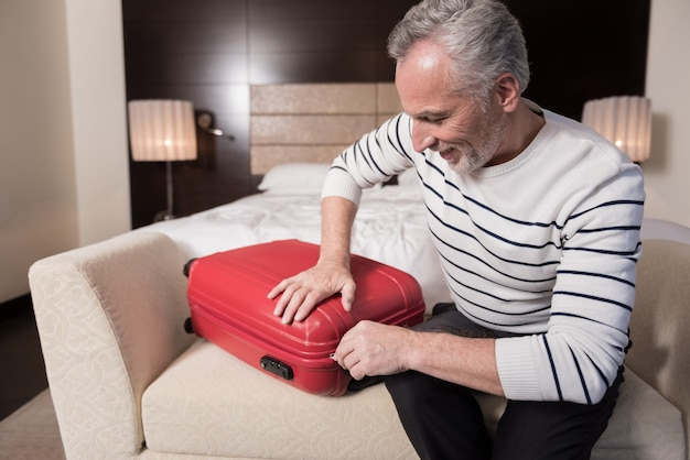 最後の準備。ソファに座って、喜びを表現しながら旅行のために荷物を集めて喜んでいる老人の笑顔