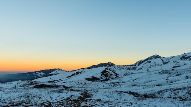 雪に覆われた山頂の最後の太陽光線