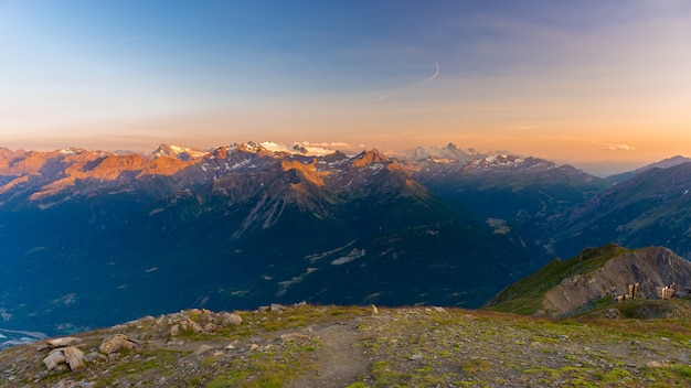 Last soft sunlight over mountain peaks, ridges and valleys of the alps at sunrise